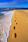 Footprints in sand along the surf at Tunnels Beach, Na Pali Coast, Island of Kauai, Hawaii