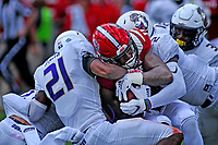 Wolfpack running back Reggie Gallaspy protects the ball as JMU defenders pull him down after a first down run.