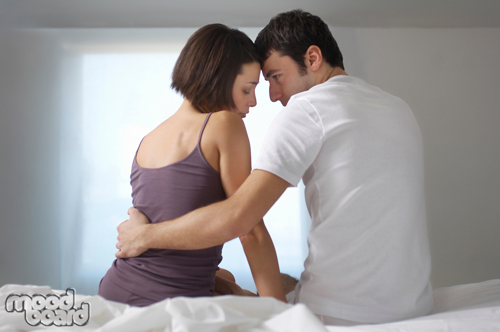Couple embracing sitting on bed back view