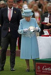 Queen Elizabeth II holds the winner's trophy at the end of the Cartier Trophy at the Guards Polo Club, Windsor Great Park, Surrey.