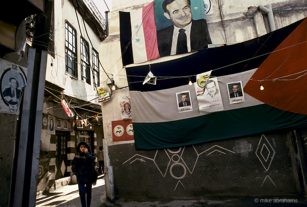 'PERSONALITY CULT OF ASSAD', STREET SCENE WITH WOMAN WALKING PAST BUILDING DRAPED WITH BANNERS SHOWING PORTRAIT OF ASSAD DURING THE REFURENDUM CAMPAIGN, DAMASCUS, DECEMBER 1991