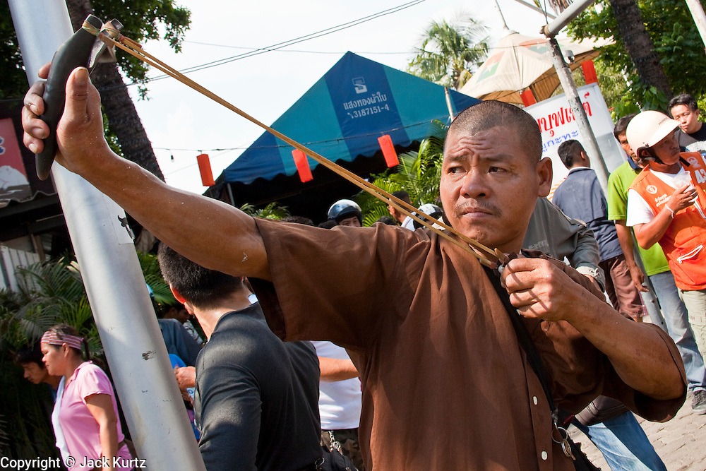 14 MAY 2010 - BANGKOK, THAILAND: Thais use slingshots to launch rocks and small home made explosives called ping pong bombs towards Thai troops on Rama IV in Bangkok Friday afternoon. Thai troops and anti government protesters clashed on Rama IV Road Friday afternoon in a series of running battles. Troops fired into the air and at protesters after protesters attacked the troops with rocket and small homemade explosives. Unlike similar confrontations in Bangkok, these protesters were not Red Shirts. Most of the protesters were residents of nearby Khlong Toei slum area, Bangkok's largest slum area. The running battle went on for at least two hours.   PHOTO BY JACK KURTZ