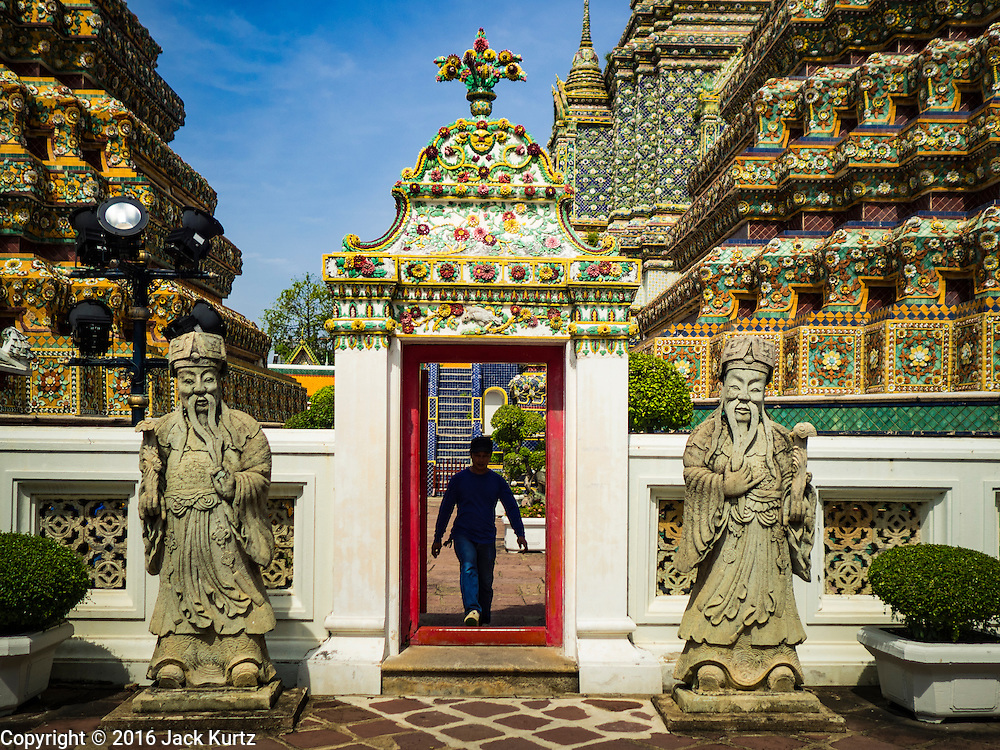 11 AUGUST 2016 - BANGKOK, THAILAND:   A man walks through the gate to one of the interior courtyards at Wat Pho in Bangkok. Wat Pho (the Temple of the Reclining Buddha), is formally known as Wat Phra Chetuphon. It's one of the largest temple complexes in Bangkok and best known for the giant reclining Buddha that measures 46 metres long and is covered in gold leaf. There is also a large ordination hall and the best known massage school in Thailand on the temple grounds.        PHOTO BY JACK KURTZ