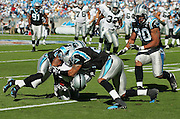 CHARLOTTE, NC - NOVEMBER 7:  The Carolina Panthers defense gang tackles an unidentified Oakland Raiders running back as Panthers teammate Julius Peppers #90 looks on at Bank of America Stadium on November 7, 2004 in Charlotte, North Carolina. The Raiders defeated the Panthers 27-24. ©Paul Anthony Spinelli  *** Local Caption *** Julius Peppers