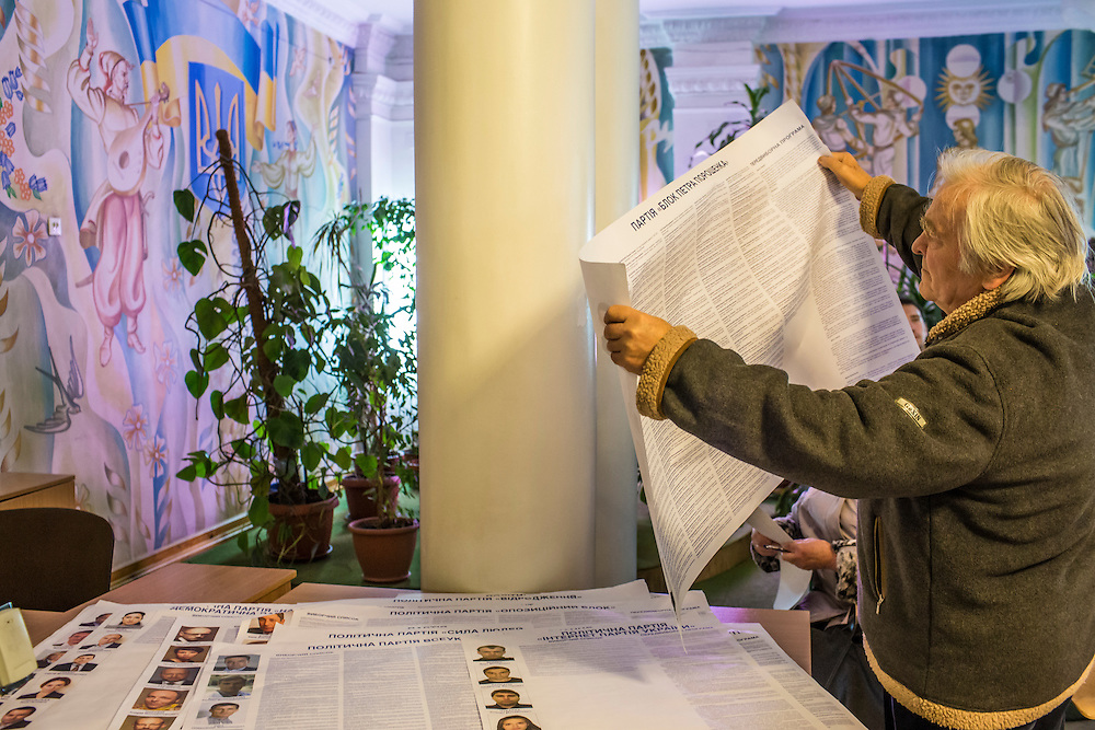 KIEV, UKRAINE - OCTOBER 26: A man at a polling station reviews an informational poster about candidates for Parliament during nationwide parliamentary elections on October 26, 2014 in Kiev, Ukraine. Although a low turnout is expected in the east of the country amid continued fighting between Ukrainian forces and pro-Russian separatists, Ukraine is expected to elect a pro-Western parliament in a further move away from Russian influence. (Photo by Brendan Hoffman/Getty Images) *** Local Caption ***