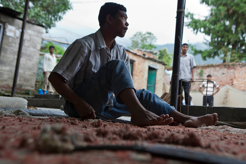 A male Nepalese factory worker trims the loose threads to finish the carpet making process.  He works in a semi-sheltered outdoor area at the R.C Rug Factory in the Narayanthan area of Kathmandu, Nepal.  These rugs are exported to Europe the U.S and Canada.