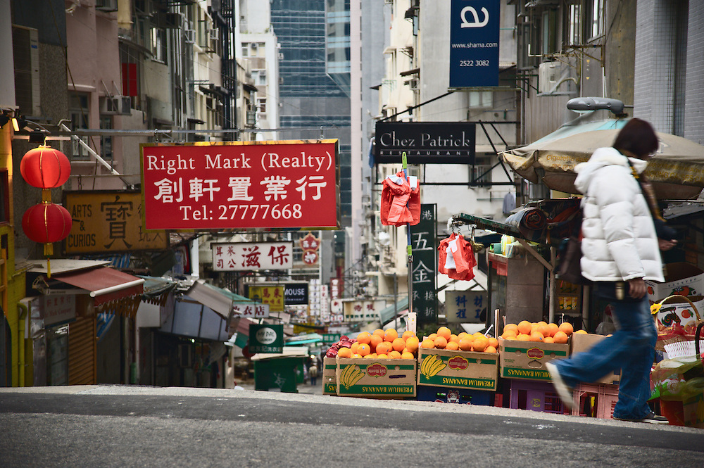 Hong Kong street with colorful signs and fruit stand