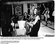 Benedict Cardona (foreground sitting on table) Graydon Carter & Wendy Stark in background. Swifty Lazar's last Oscar Night  Party. Spago's. Los Angeles. March 1993. Film. 93244/13<br />