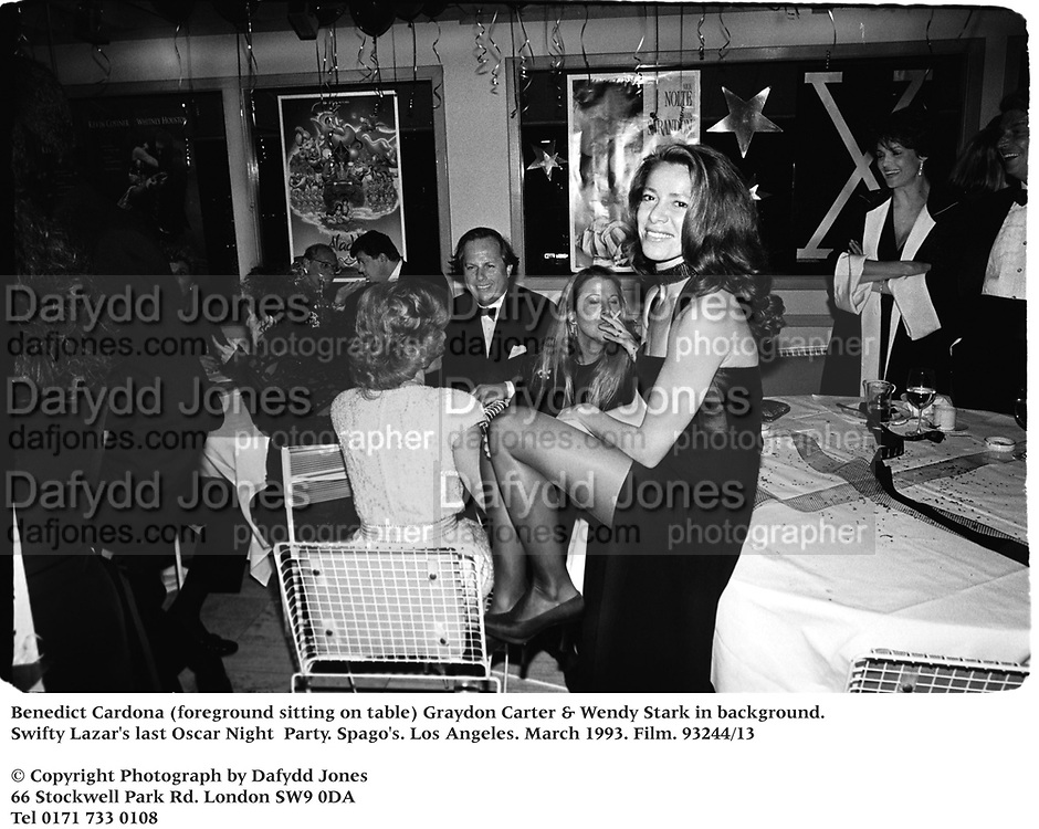 Benedict Cardona (foreground sitting on table) Graydon Carter & Wendy Stark in background. Swifty Lazar's last Oscar Night  Party. Spago's. Los Angeles. March 1993. Film. 93244/13<br /><br />© Copyright Photograph by Dafydd Jones<br />66 Stockwell Park Rd. London SW9 0DA<br />Tel 0171 733 0108