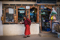 PARO, BHUTAN - CIRCA OCTOBER 2014: Woman walks in front a general store in Paro, Bhutan