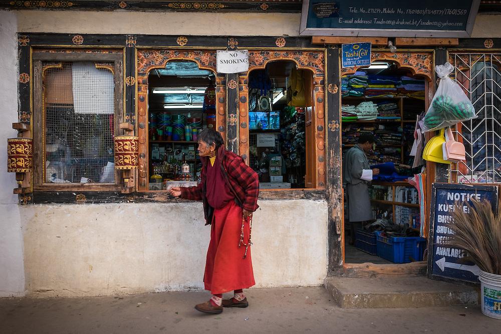 PARO, BHUTAN - CIRCA OCTOBER 2014: Woman walks in front a general store in Paro, Bhutan