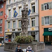 Two artists lean against fountain in center of Weinmarketgasse, Luzern, Switzerland<br />