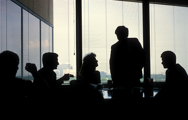 Stock photo of the silhouette of an afternoon business meeting taking place in a corporate office