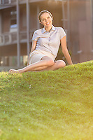 Smiling young businesswoman relaxing in office lawn