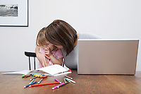 Mother sonsoling sad daughter (3-4) open laptop on table