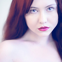 Close up of young woman's face with red hair looking into camera
