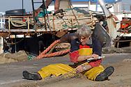 Anzio, Italy 24/04/2003: pescatori sistemano le reti sulla banchine del porto