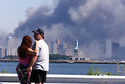 The Statue of Liberty with the smoke from the World Trade Center fire. A couple stop to watch near the Marine Terminal in Bayone.