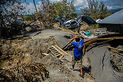 Oct. 2, 2018 - Palu, Indonesia - A man walks by the debris of houses in Petobo village in Sigi district of Central Sulawesi after the deadly earthquake and tsunami in Central Sulawesi, Indonesia. Over 1,234 people were killed in Palu, Donggala district, Parigi Mountong district and North Mamuju district, according to the Disaster Management Institute of Indonesia, Care for Humanity and the Humanity Data Center. (Credit Image: © Iqbal Lubis/Xinhua via ZUMA Wire)