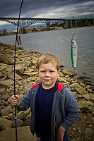A young boy fishes in the Willamette River in Portland, Oregon