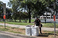 A police officer fixes the bag on a trash can on Monday, September 3, 2012 in Charlotte, NC.