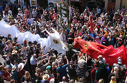 © Licensed to London News Pictures. Glastonbury, Somerset. Sunday 6th May 2018. Hundred of people watch as The Glastonbury Dragons process through the high street heading for Glastonbury Tor during the Beltane May Day celebrations. Photo credit: Jason Bryant/LNP