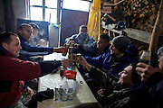 Locals from Strpce drinking Rakija after they have collected the traditional Serbian christmas trees.