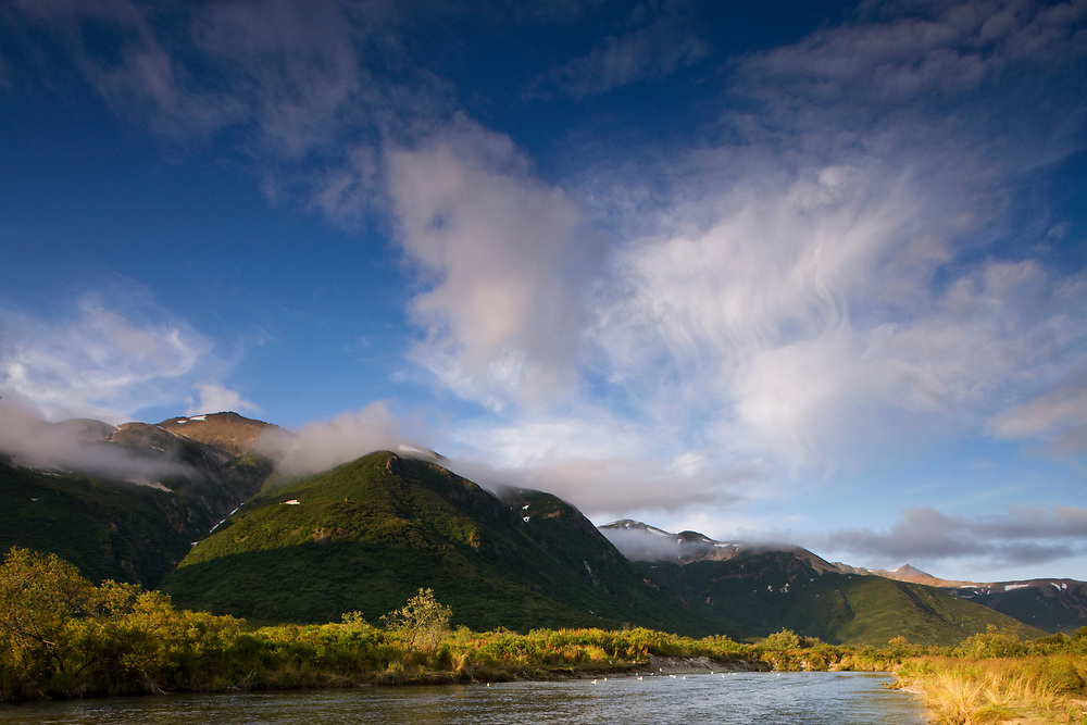 USA, Alaska, Katmai National Park, Kinak Bay, Setting sun lights mountain peaks on autumn evening