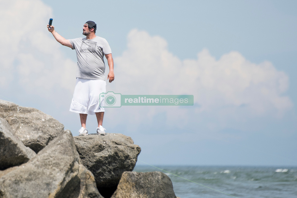 September 6, 2017 - West Palm Beach, Florida, U.S. - German Raljevic, a 44-year-old from Brooklyn, records a video message for his New York friends while standing on a rock at Jupiter Park Beach. Raljevic said his friends told him to leave Florida before Hurricane Irma's arrival, and that the video message was his goodbye to them. (Credit Image: © Andres Leiva/The Palm Beach Post via ZUMA Wire)