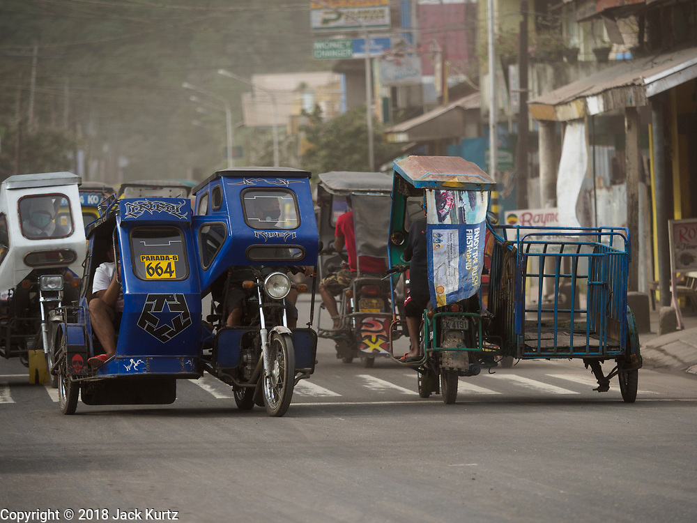 24 JANUARY 2018 - GUINOBATAN, ALBAY, PHILIPPINES:  Traffic during a volcanic ash fall in Guinobatan. The Mayon volcano continued to erupt Tuesday night and Wednesday forcing the Albay provincial government to order more evacuations. By Wednesday evening (Philippine time) more than 60,000 people had been evacuated from communities around the volcano to shelters outside of the 8 kilometer danger zone. Additionally, ash falls continued to disrupt life beyond the danger zones. Several airports in the region, including the airport in Legazpi, the busiest airport in the region, are closed indefinitely because of the amount of ash the volcano has thrown into the air.   PHOTO BY JACK KURTZ