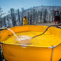 Firefighters fill a pool of water to pump from as the Holcomb Fire burns in the Holcomb Valley are of the San Bernardino National Forest near Big Bear, Tuesday, June 20, 2017. (EricReed/For The Sun/SCNG)