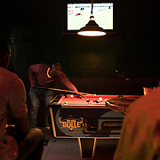 Men are playing pool at the bar-restaurant « La Camerounaise » in Yeoville, Johannesburg. The place is a popular meeting place for the French-speaking African community that has settled in or around the city of Johannesburg. Once a white Jewish area, Yeoville has become a Pan-African village populated by Black South Africans and African migrants. 19 November 2016 Johannesburg, South Africa. © Miora Rajaonary