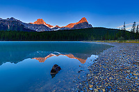 Alpenglow on the mountain peaks surrounding Upper Waterfowl Lake at Sunrise with the mountains reflected the glassy calm waters of the lake.<br /> <br /> ©2015, Sean Phillips<br /> http://www.RiverwoodPhotography.com