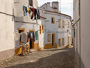 Residential buildings in cobbled street with historic whitewashed houses, washing hanging drying, bicycle leaning against a home. An image of city life one of the old neighbourhoods in the city centre of Evora, Alto Alentejo, Portugal, southern Europe