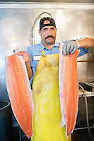 Portrait of mature fishmonger holding sliced salmon