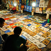 A vendor shows a customer his range of paintings, drawings, and other illustrated art at the night market on Quai Fa Ngum on the banks of the Mekong in Vientiane, Laos.