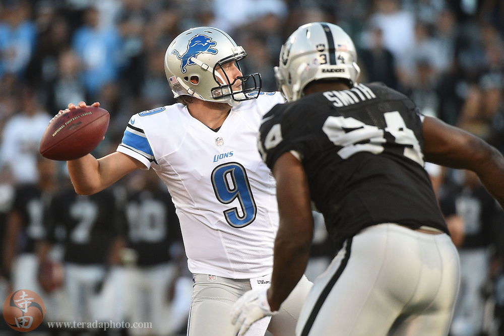 August 15, 2014; Oakland, CA, USA; Detroit Lions quarterback Matthew Stafford (9) passes the football against Oakland Raiders defensive end Antonio Smith (94) during the first quarter at O.co Coliseum.
