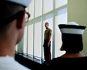 "A United States Marine oversees some of the freshmen as they are processed on their first day at the U.S. Naval Academy in Annapolis, MD. Approximately 1,230 young men and women arrived at the U.S. Naval Academy's Alumni Hall, Thursday, July 1, for Induction Day to begin their new lives as ""plebes"" or midshipmen fourth class (freshmen). ""I-Day"" culminates when the members of the Class of 2014 take the oath of office at a ceremony at 6 p.m. in Tecumseh Court, the historic courtyard of the Bancroft Hall dormitory. Over 17,400 young men and women applied to be members of the Naval Academy Class of 2014 - a record for USNA."