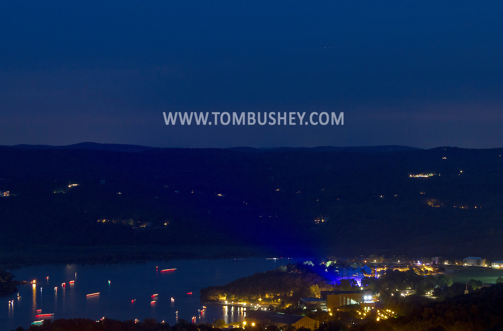 West Point, New York - Boats, at lower left, gather in the Hudson River, at left, to watch the fireworks display in the sky over the U.S. Military Academy at the end of the West Point Band's Fourth of July Celebration Concert on July 8, 2012. The blue light at lower right is coming from the concert at Trophy Point. The photograph was taken from the Route 9W overlook.