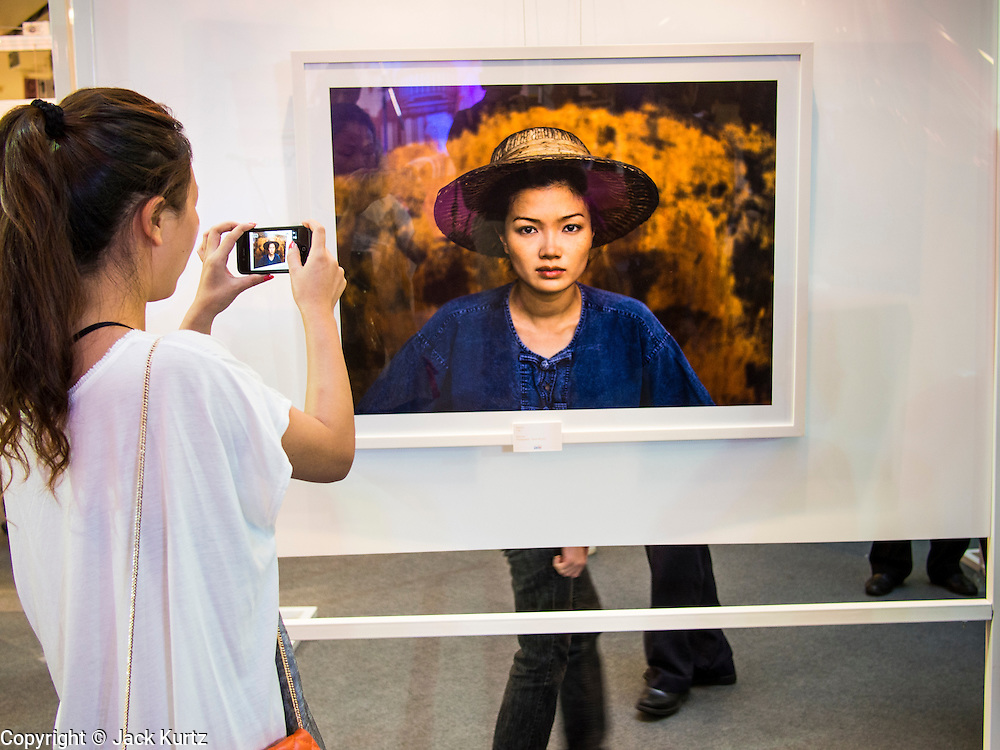 19 JULY 2013 - BANGKOK, THAILAND:  A Thai woman takes a picture of a Steve McCurry photo hanging in a show in CentralWorld in Bangkok. The US Embassy in Bangkok sponsored the photo exhibit, which celebrates 180 years of US-Thai diplomatic relations. There are 180 photos hanging in the show, 90 by American photographers in Thailand and 90 by Thai photographers in the United States. The show, which opened July 19, is hanging in CentralWorld, a large mall in Bangkok, and is touring Thailand when it concludes its Bangkok run on July 21.    PHOTO BY JACK KURTZ