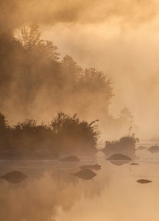 Warm light breaks through the early morning fog on Marshfield Pond, Marshfield, Vermont