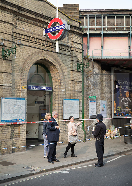 © Licensed to London News Pictures. 17/10/2017. London, UK. Commuters talk to a policeman near where a man was stabbed. Police are investigating after a man in his 20's was stabbed to death and two others were injured in an incident on Monday night outside Parsons Green underground station a terrorist attack took place last month. Photo credit: Peter Macdiarmid/LNP