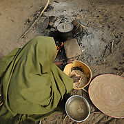 Adama Garba prepares the evening meal at her home in the village of  Nakaidabo in the Tessaoua region of Niger. She has only the handfuls of beans in her calabash and a pinch of salt to feed her family of seven.