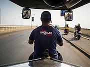 "26 FEBRUARY 2015 - PHNOM PENH, CAMBODIA:  A tuk-tuk driver with a ""True American"" tee shirt drives his tuk-tuk over the Cambodia-Japan Friendship Bridge spanning the Tonle Sap River in Phnom Penh.   PHOTO BY JACK KURTZ"