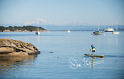 A young boy paddles a stand-up paddleboard at Sucia island, a Washington state park, with Mount Baker seen in the background.