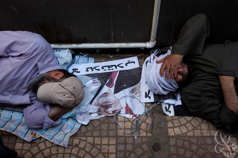 Supporters of deposed Egyptian president Mohamed Morsi march sleep on a poster of the ex-leader as they maintain their now month long sit-in around the Rabaah al-Adawia mosque and square in the Nasr City district of Cairo Friday July 26, 2013.  The supporters are demanding the reinstatement of the deposed President and are opposed to the Egyptian military, which they say has undertaken an undemocratic coup.