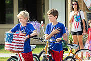 Young boys stand for the national anthem before the start of the annual Independence Day golf cart and bicycle parade July 4, 2019 in Sullivan's Island, South Carolina. The tiny affluent Sea Island beach community across from Charleston holds an outsized golf cart parade featuring more than 75 decorated carts.