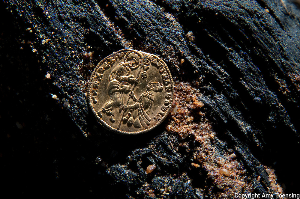 ORANJEMUND, NAMIBIA -- OCTOBER 04: One of the 3 Excellentes coins, which display inscriptions of King Ferdinand and Queen Isabella, known for uniting Spain in the early 1500s found on October 04, 2008 in Oranjemund, Namibia. The wreck was uncovered by miners in the Namdeb diamond mine off the coast of Namibia. The ship was found seven meters below sea level on April 1, 2008. Archeologists presume the wreck is from the early 1500s. Most of the the artifacts found are being stored in a storage shed at the Namdeb Diamond Mine. Items include: copper ingots, bronze canons, canon balls, pewter bowls and plates, ivory tusks from African elephants, and most substantial over 2000 gold coins - approximately 21 kg - the most gold found in Africa since the Valley of the Kings in Egypt. (Photo by Amy Toensing) _________________________________<br /> <br /> For stock or print inquires, please email us at studio@moyer-toensing.com.