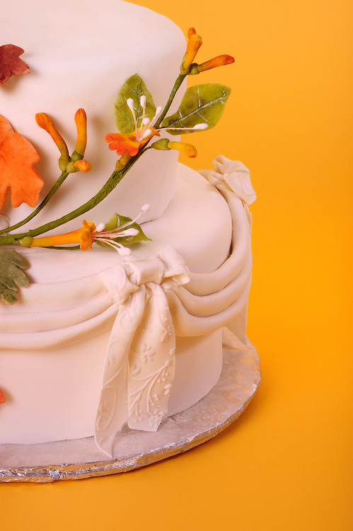 Detail of Autumn Wedding Cake with orange red yellow and gold marzipan leaves and flowers and decorated marzipan lace ribbon on golden yellow background with copy space