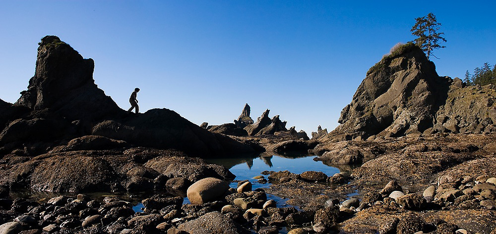 Zach Podell-Eberhardt climbs over rocks along the rugged coastline at Shi Shi Beach, Olympic National Park, Washington.